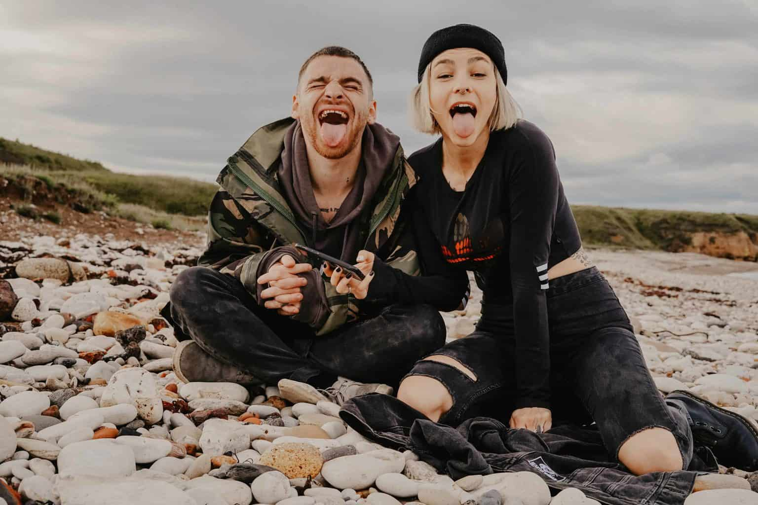 Silly couple on a pebbled beach, making wacky faces.