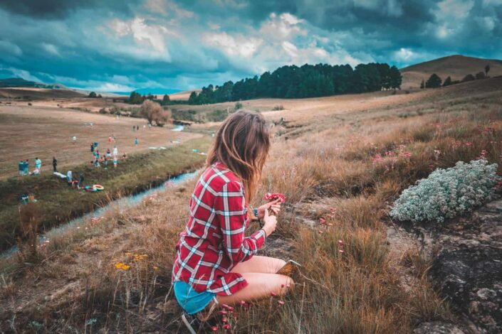 Girl picking flowers on a hill.