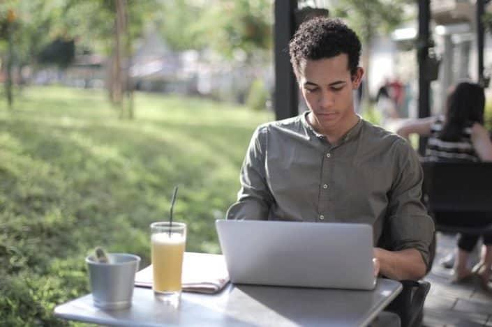 Focused black male freelancer using laptop in street cafe