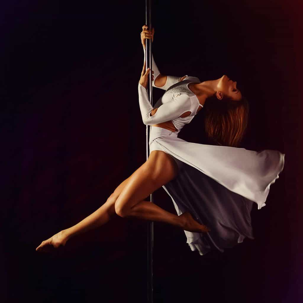 Girl passionately dancing on a pole.