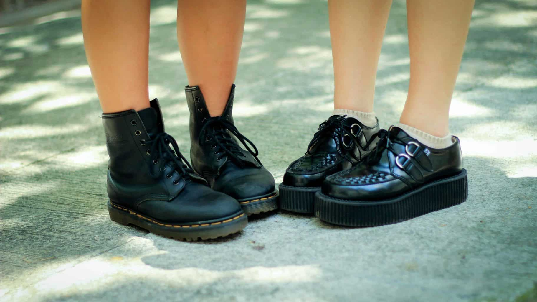 Two pairs of leather shoes worn by kids.