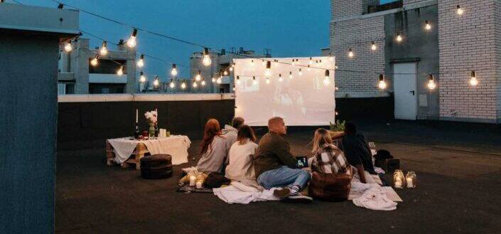 Friends having a movie night on rooftop