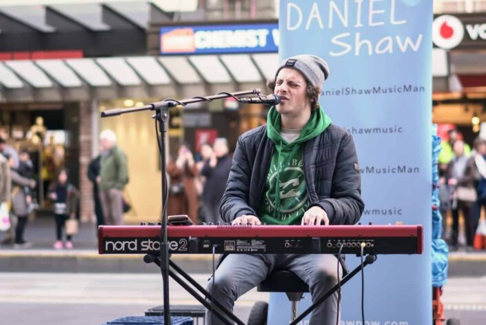 Guy performing on a street playing keyboards and singing