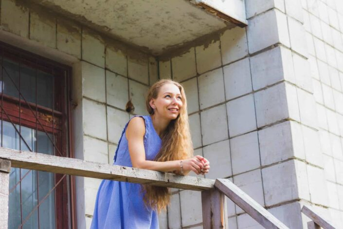 Girl standing on the balcony smiling