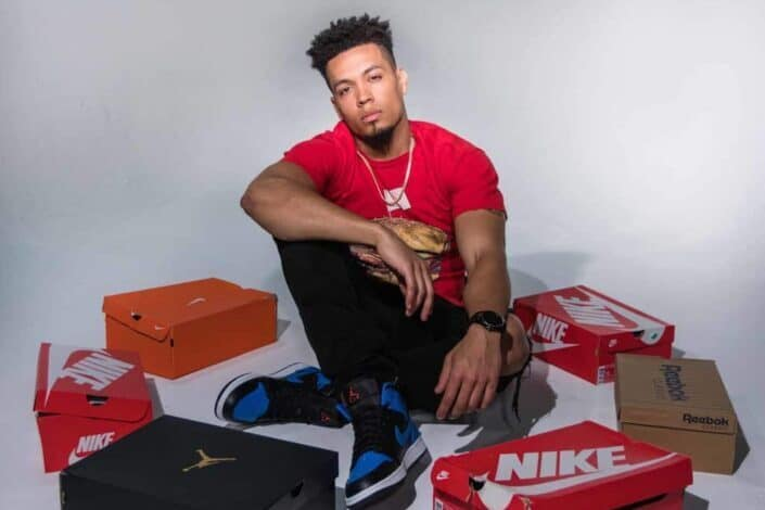 Man sitting with boxes of shoes