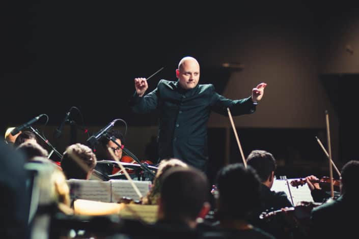 What is the name given to the person who directs the orchestra? Answer: Conductor.jpg