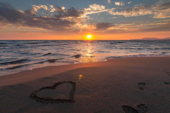 A heart on the sand with a beautiful sunset view.