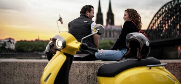 couple sitting in front of scooter