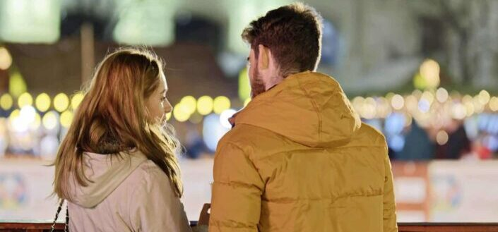 couple leaning on a railings while talking