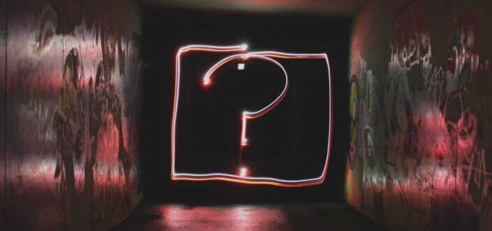 A shot of question mark written with a neon light.