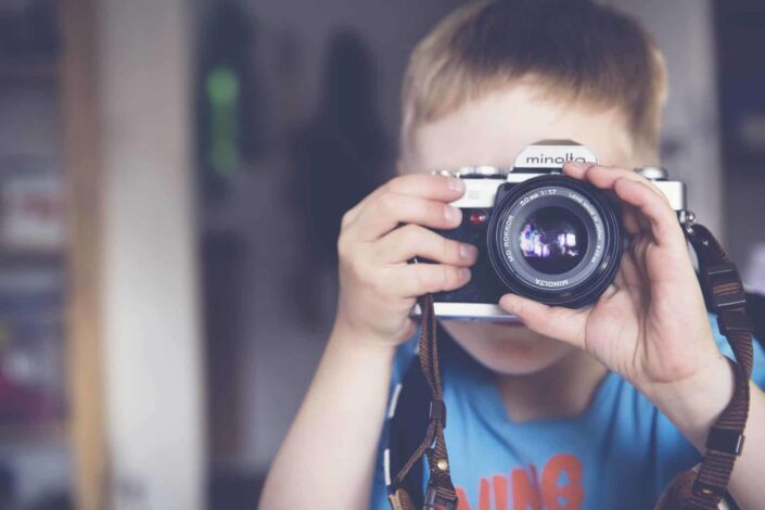 A little boy taking picture with camera