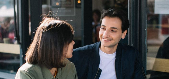 Guy smiling while talking to a girl.