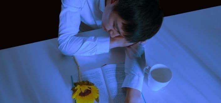 man napping on table with mug and book