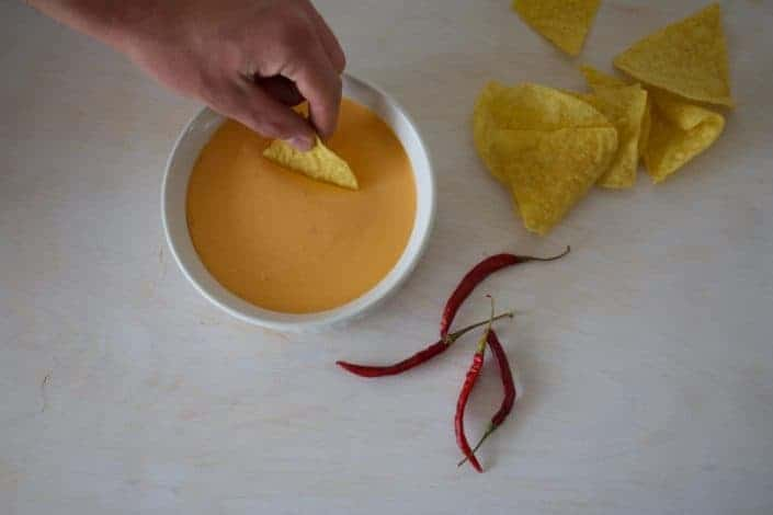 Chips dipped in cheese with chillis