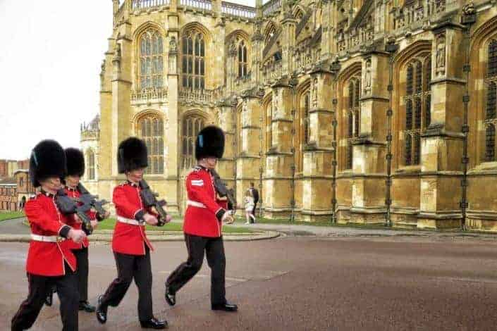 Uniformed royal guards marching outside