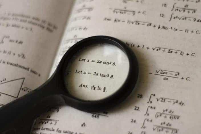 Magnifying glass focused on an algebraic formula
