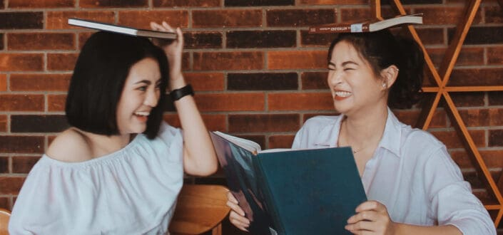 two women being playful with the books