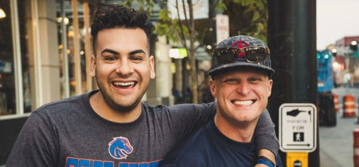 two men standing in street and smiling happily