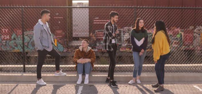Teens talking outside by the street
