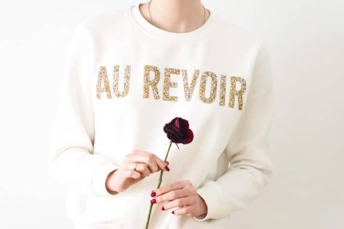 woman in white sweater holding dark red rose