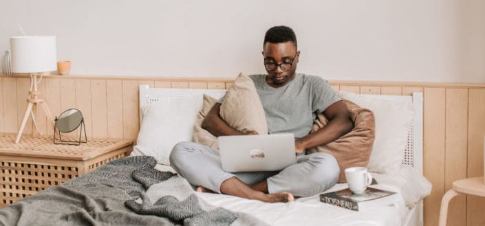 Man sitting on a bed and using his laptop