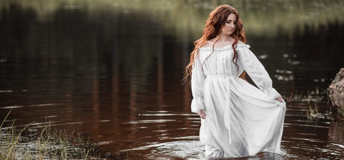 Redhead girl in white dress standing in a lake.