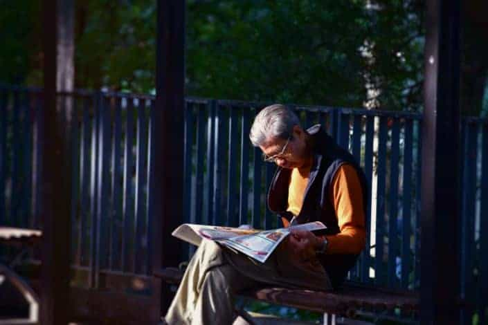 An old man sitting on a bench, reading a newspaper.