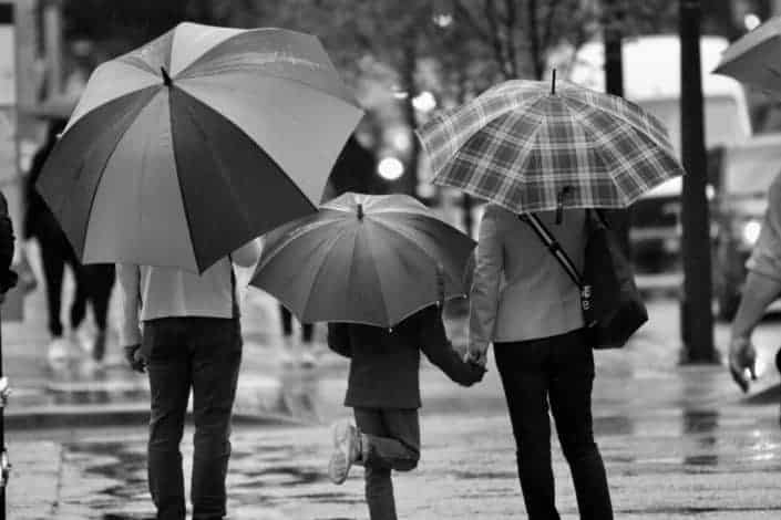 grayscale photography of family holding umbrella