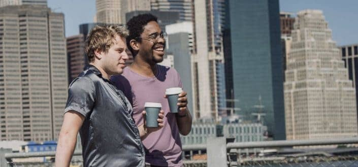 Two guy friends sharing a cup of coffee outdoors.