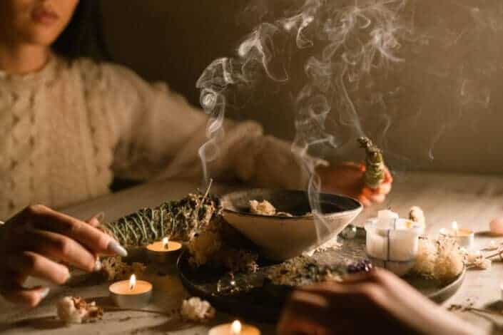 woman burning herbs with candles