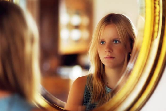 woman with blue eyes staring at her reflection