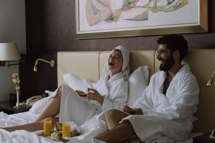 couple wearing robes having breakfast in bed