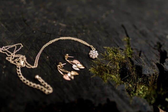 gold necklace and earrings next to green moss