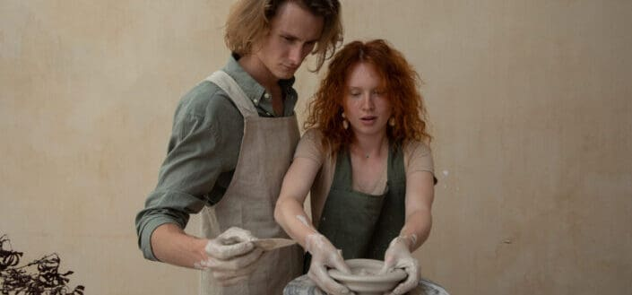 man standing next to a woman making pottery