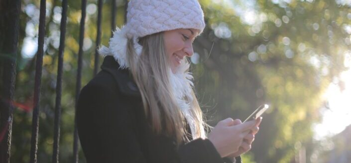 Girl reading text from her phone outdoors.