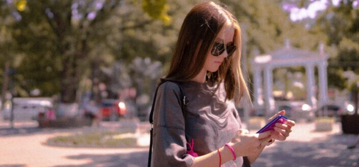 Girl walking and looking down to read a text.