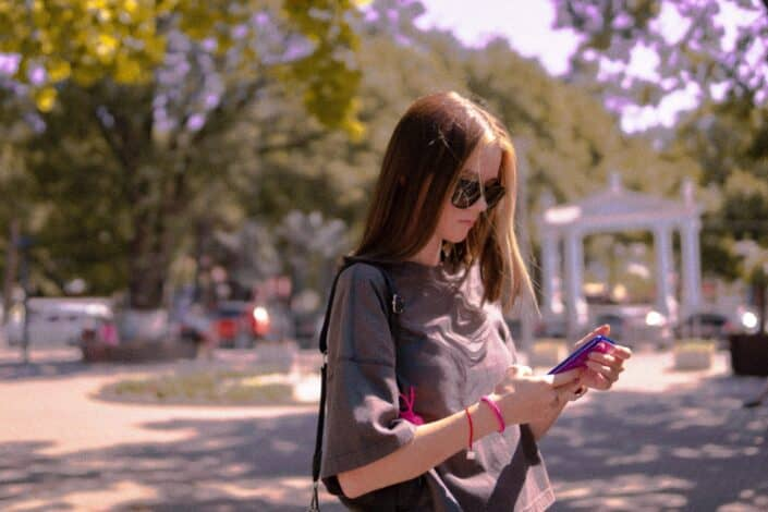 A lady with sunglasses, texting while outdoors.