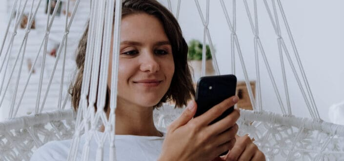 Girl sitting in a white swing smiling at her phone.