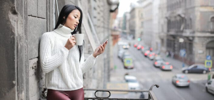 Girl reading text on her phone on a ledge with a cup of coffee.