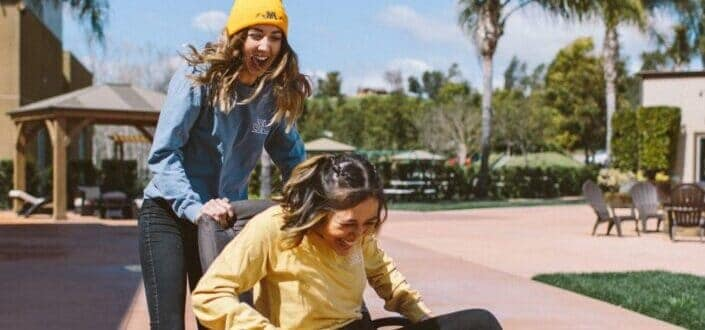 two laughing women sitting on rolling chair