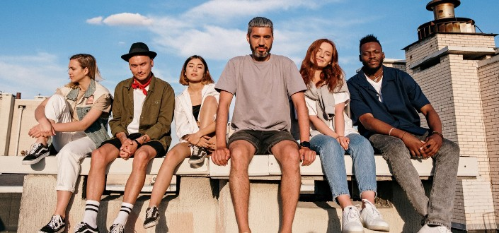 Group of people sitting on white concrete bench