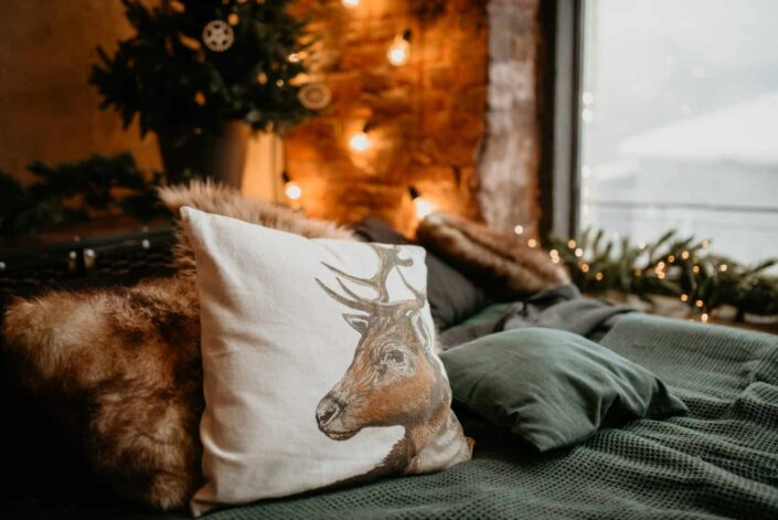 white throw pillow printed with a deer design on a cozy couch