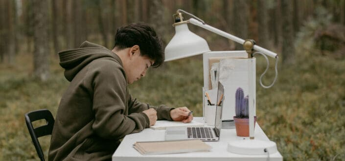 A man working on a desk in the middle of the forest