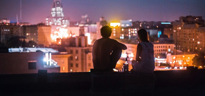 couple on rooftop looking at city lights