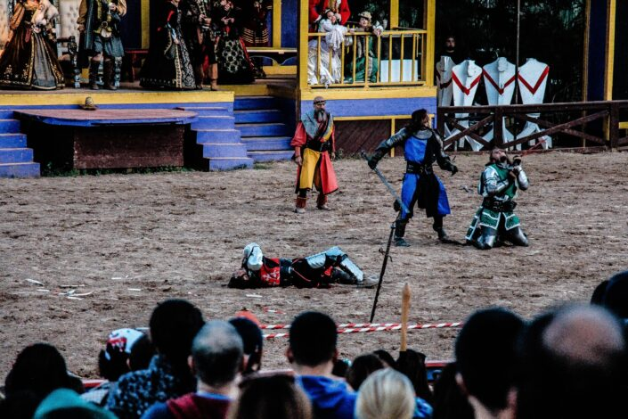 four men in renaissance outfits on a fair ground acting out a play