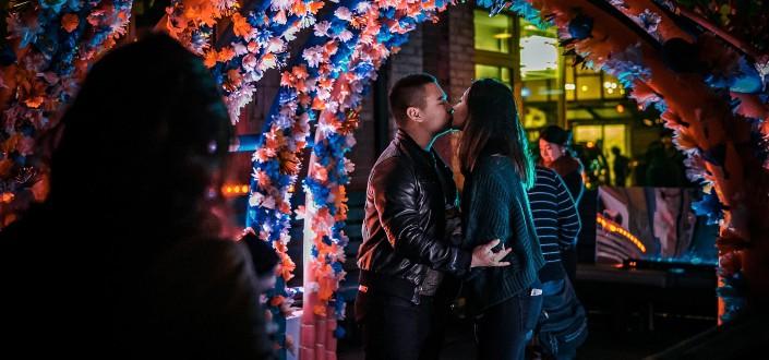 man and woman kissing under a flower gazebo