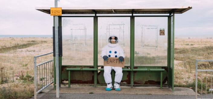 Astronaut-attired person holding a sign