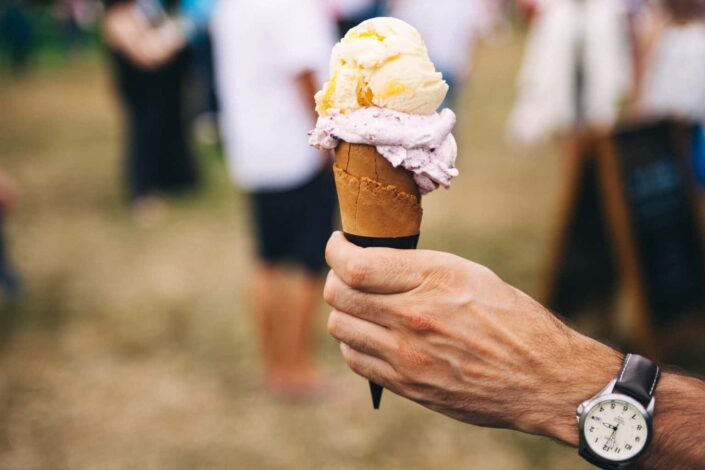 man's hand holding a cone of ice cream