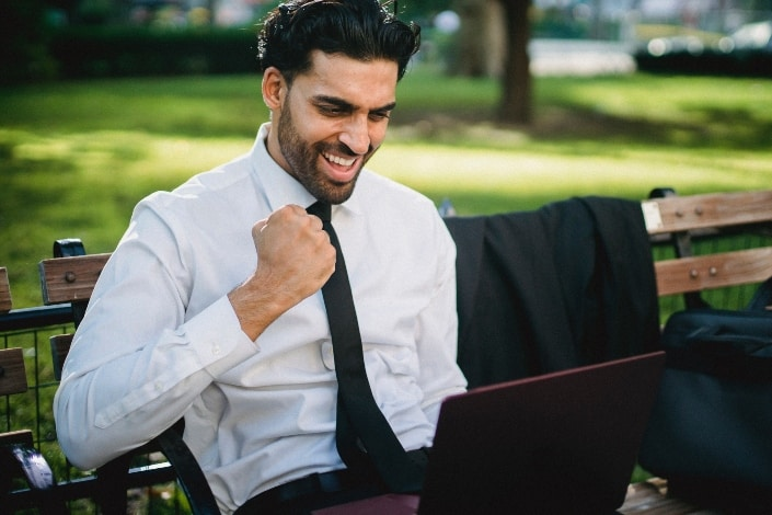 man smiling widely with his fist slighty up