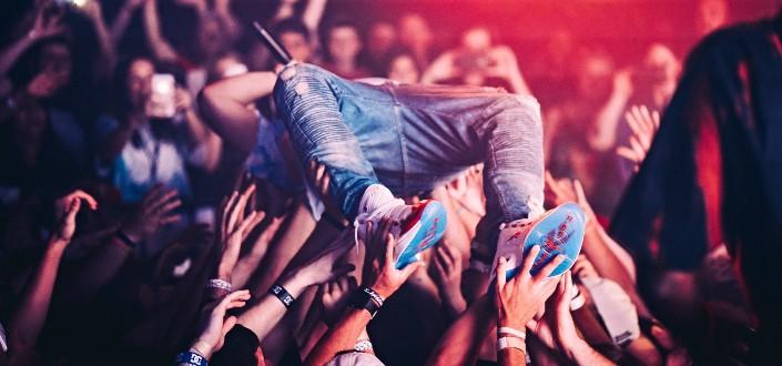 male singer in jeans crowd surfing